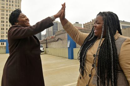 "Nykidra ""Nyki"" Robinson of Baltimore, left, high fives Tiffany Simpson of Belcamp, after Robinson explained her new group, ""Black Girls Vote."""