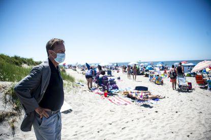 Gov. Ned Lamont looks along the shoreline at beachgoers enjoying time at Hammonasset Beach Thursday, July 2, 2020, in Madison.