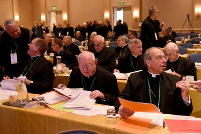 Archbishop William E. Lori, seated at right, and other bishops prepare for the second day of the fall session of the U.S. Conference of Catholic Bishops in Baltimore.