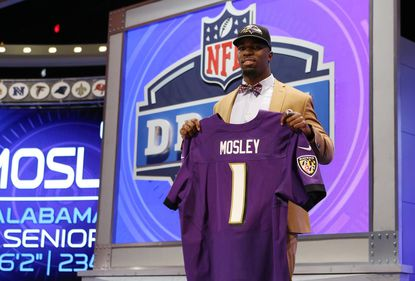 Inside linebacker C.J. Mosley poses for photos with his Ravens jersey after being taken in the first round of the NFL draft.