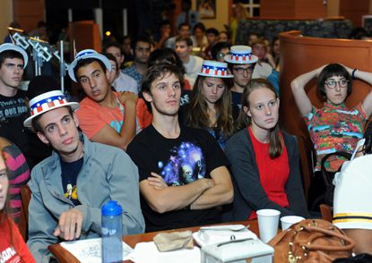 Johns Hopkins University seniors, from left, Archibald Henry, of New York; Nicholas DePaul, of California; and Anna Kleinsasser, of Baltimore, along with others, watch the first presidential debate at one of the campus dining halls.