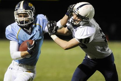 River Hill's Evan Griffin fends off a tackle attempt by Urbana's Pat Coffey in the 3A state semifinal game at River Hill Nov. 23.