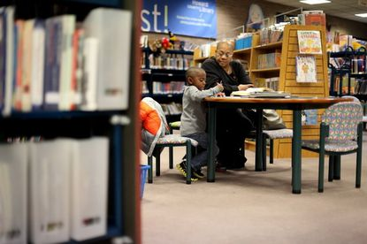 Gavin Banks, left, 5, colors with his grandmother Linda Clifton both of Laurel (Howard County side) at the Savage Library in Savage, MD. The library, which has undergone renovations, will open a temporary branch on Aug. 26.