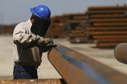 A workergrinds a steel pipe Monday at the Borusan Mannesmann plant in Baytown, Texas.
