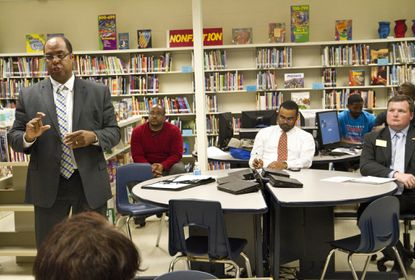 Rainier Harvey speaks to residents during a District 44B candidates' forum at Edmondson Heights Elementary School on May 9, 2014, while Charles Sydnor, at center, and Pat Young, right, wait at the table for their turn to speak.