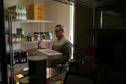 Dr. Ed Hartman deposits donated food in the storage room at the Community Crisis Center, Nov. 8.