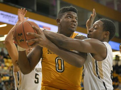 St. Frances' Eric Cobb is challenged by John Carroll defenders as he drives to the basket in the second half.