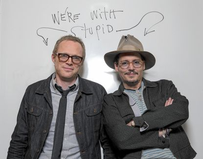 """Johnny Depp, right, poses with Paul Bettany after writing """"we're with stupud"""" on a whiteboard at the Four Seasons Hotel while promoting the movie """"Transcendence."""""""