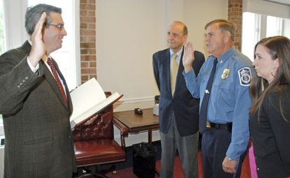 Larry W. Tolliver was sworn in as chief of the Anne Arundel County Police in 2012 while his daughter Danielle Kane and then-County Executive John R. Leopold looked on. Administering the oath was county Circuit Court Manager Doug Arnold. (File/Capital Gazette).