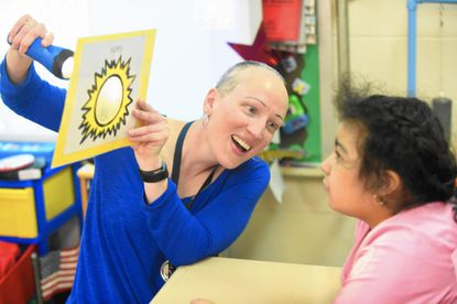 Amy Mangold, HCPS teacher of the year, shines a flashlight thru a picture of a sun as she discusses the day's weather with 5 year-old student Marielos Flores-Escalante during morning class time at John Archer School on Wednesday, April 19.