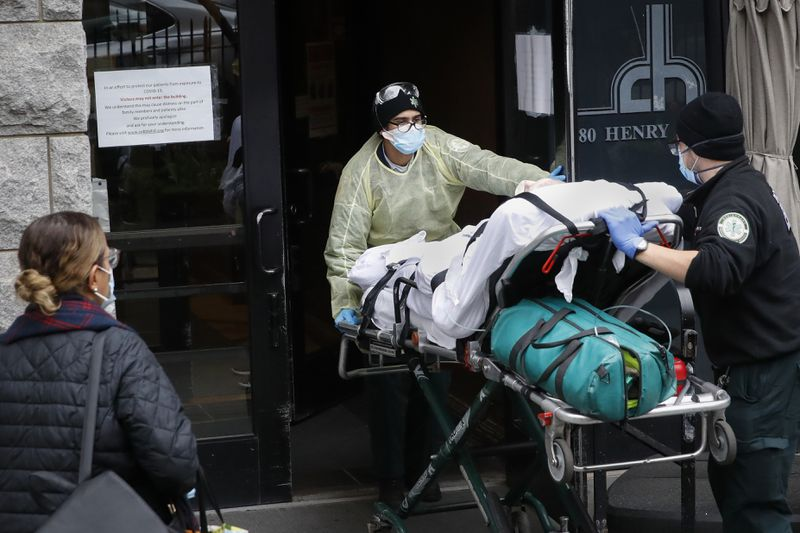 A patient is wheeled into Cobble Hill Health Center by emergency medical workers in Brooklyn on April 17, 2020.