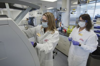 In this May 2020 photo provided by Eli Lilly, researchers prepare cells to produce possible COVID-19 antibodies for testing in a laboratory in Indianapolis. Antibodies are proteins the body makes when an infection occurs; they attach to a virus and help it be eliminated.(David Morrison/Eli Lilly via AP)