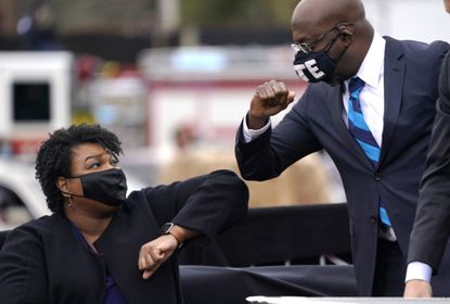 U.S. Senate-elect Raphael Warnock bumps elbows with Stacey Abrams (L) during a campaign rally with U.S. President-elect Joe Biden at Pullman Yard on December 15, 2020 in Atlanta, Georgia.
