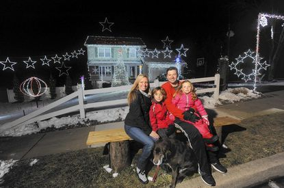 Angie and Bryan Bartlett, their son, Bryson, 8, and daughter, Brynn, 5, and the family dog, Sydney, have an elaborate Christmas light display at their home that is in sync with 38 different songs. Hundreds of car stop by every night to view the display which have over 20,000 lights.