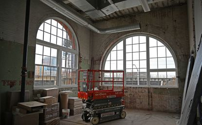 Grand windows in the Hoen Lithography building overlook the Amtrak line along Biddle Street in East Baltimore.