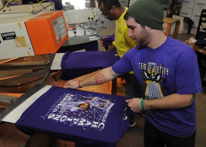 Nightmare Graphics' Josh Rufenacht pulls a shirt from a machine after it's been screen painted. In the background is Asfaw Mengstu.