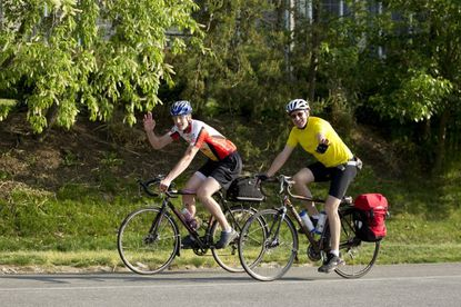 Cyclists Aaron Fields, of Columbia, and Fran Horan, right, of Ellicott City, wave as they ride along Martin Road while biking to work in Columbia last year.