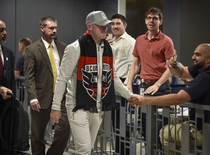 Wayne Rooney greets fans as he arrives at Dulles Airport. MUST CREDIT: Washington Post photo by Bill O'Leary