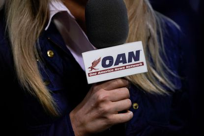 A reporter with One America News Network works at a campaign rally with President Donald Trump at Newport News/Williamsburg International Airport on September 25, 2020 in Newport News, Virginia.