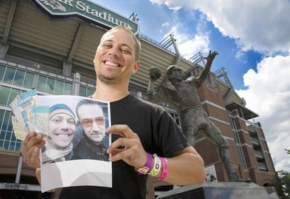 Jason Siemer of Locust Point poses with wrist bands and tickets to past concerts in front of the football stadium and a photo of himself with lead singer Bono Friday.
