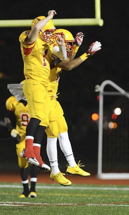 Calvert Hall quarterback Thomas Stuart, left, celebrates with receiver Trevor Williams after connecting on a touchdown pass during the Cardinals' 29-23 victory on Friday night at Paul Angelo Russo Stadium in Towson.