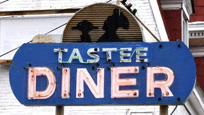 The Tastee Diner's blue neon sign stands high along Washington Blvd. in the diner's parking lot.