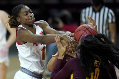 Maryland guard Diamond Miller, left, competes for a rebound with Minnesota forward Kadiatou Sissoko (30) and center Klarke Sconiers during the second half of an NCAA college basketball game, Saturday, Feb. 20, 2021, in College Park, Md. (AP Photo/Julio Cortez)
