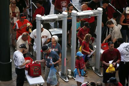 Fans arrive at Chase Field in Phoenix to new MLB security measures. Similar measures will be in effect at Camden Yards.