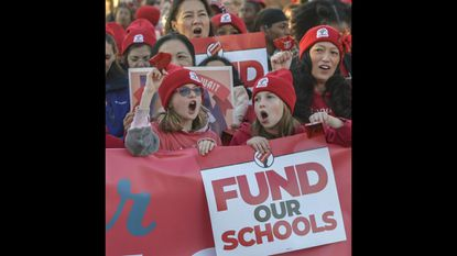 Severna Park Elementary School fourth graders Lila Gagnier, left, and Ellie Brown join thousands of teachers, parents and students in Annapolis in March to rally for a school funding bill. Maryland Gov. Larry Hogan says he will let the bill become law.