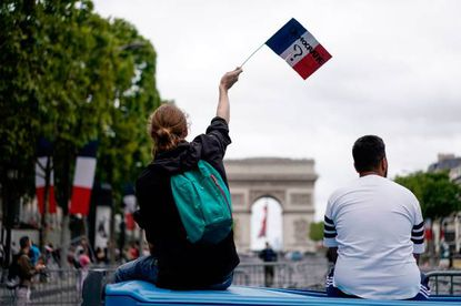 """A protester linked to the Yellow Vests (Gilets Jaunes) movement holds a French flag reading """"Democracy?"""" as he sits in front of the Arc de Triomphe on the Champs-Elysees in Paris on the side of the annual Bastille Day ceremony, on July 14, 2019."""