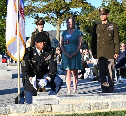Sgt. 1st Class Losivale Tally , front, places the stone engraved with First Lt. Dax Conrad's name in its place within the Gold Star Memorial as , from left, CSM Kristie Brady, widow Emily Zembas, and MG Robert Edmonson II look on during the Aberdeen Proving Ground 2021 Gold Star Mother's and Family's Day ceremony at the Living Legacy Pavillion Friday October 1, 2021.