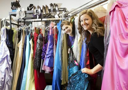 Krystal Hastings, left, a fourth-year student at Howard Community College, and Brittany Budden, Director of Service Learning at the college, go through the prom dresses collected for The Perfect Prom Project. So far, 71 dresses have been collected.