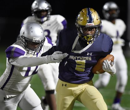 Perryville's Emarion Hampton tries to slip from the grasp of Joppatowne's Jason McLeaod during a Class 1A East playoff game at Perryville in 2019.
