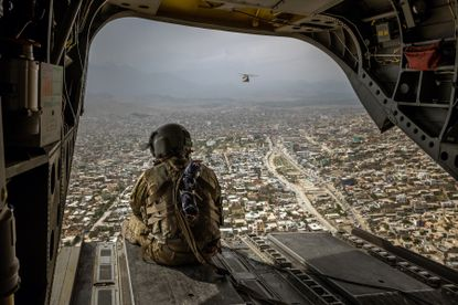 FILE -- An American soldier on a CH-47 Chinook helicopter flying over Kabul, Afghanistan's capital, on May 2, 2021. (Jim Huylebroek/The New York Times)