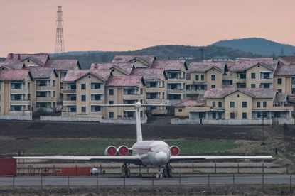 This photo taken on April 17, 2017, shows an Air Koryo aircraft as it sits parked in front of houses outside Pyongyang airport.