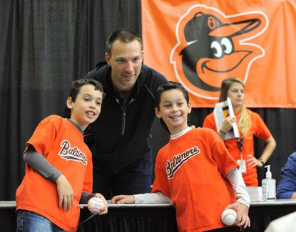 Orioles closer Jim Johnson takes a picture with twin brothers Evan and Brandon Fedock, 9, of Clarksburg.