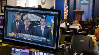 Attorney General William P. Barr is seen on TV monitors as he delivers remarks on the release of the report on the investigation into Russian interference in the 2016 presidential election.
