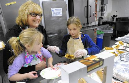 Frances McDonough of Owen Brown, who was volunteering through her church, St. John the Evangalist Catholic Church, prepares pumpkin pie with her grandchildren Kelly McDonough, left, 3, and Abby McDonough, 9, both of Stevens Forest, during the NAME Sunday Suppers program at the Florence Bain Senior Center in Columbia.