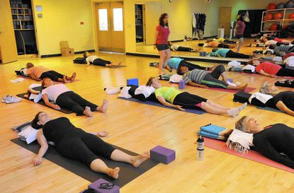 Susan Fleischer, bottom left, of Pikesville, participates in a meditation class May 28 led by Robyn Katz, standing, a yoga and meditation instructor at LifeBridge Health and Fitness in Pikesville.