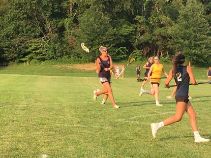 Kim Eraso of Blue Razz goes in for a score, while Gold's Marisa Parker and Blue's Gabby Eraso look on.