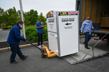 Raul Sotez, left, of Interstate Van Lines rolls a ballot drop box into place at Mount Pleasant Church on Radecke Avenue, one of five drop box locations for the primary election.