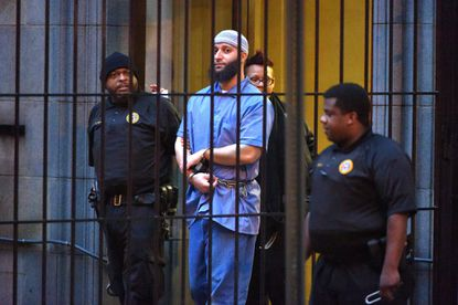 """Officials escort """"Serial"""" podcast subject Adnan Syed from the courthouse following the completion of the first day of hearings for a retrial in February.The state is opposing a request by Syed's attorneys for a bail hearing."""