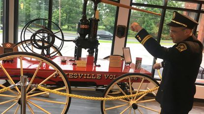 Capt. Scott Goldstein shows off the Pikesville Volunteer Fire Co.'s original 1897 water pump engine, restored and housed in the recently renovated firehouse's new museum.