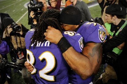 Wide receiver Torrey Smith is hugged by teammate linebacker Ray Lewis after they defeated the New England Patriots at M&T Bank Stadium.