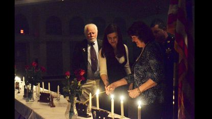 """Phil Mullikin watches as his daughter Alexandria and wife Cynthia light a candle in memory of their daughter and sister Catherine at the 12th annual """"I Will Remember You"""" Remembrance Ceremony on Thursday. Catherine was killed Nov. 28, 1998, by a drunk driver."""