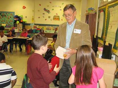 Mike Grimes of the Kiwanis Club of Reisterstown, distributes dictionaries at Glyndon Elementary School Nov. 13. More than 700 dictionaries have been distributed to area elementary schools this year. This is an ongoing project to give each third grader their own personal dictionary.
