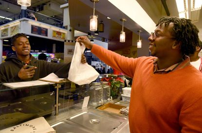 Regular customer Malcolm Dorsey of West Baltimore, left, picks up a lunch order from Khari Parker at Connie's Chicken and Waffles in Lexington Market. Khari Parker co-owns the stall with his brother Shawn.