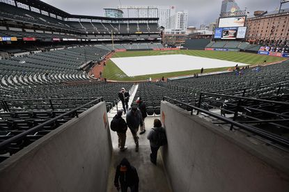 A tarp covers the infield at Camden Yards, Saturday, April 9, 2016 in Baltimore. The Orioles' game against the Rays was postponed because of inclement weather.