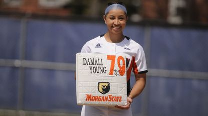 Right fielder Damali Young shows off a base in 2018 commemorating her 79th career steal, which broke Morgan State's all-time record. She now has 119 in her career.