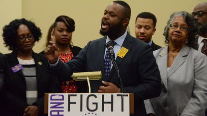Supporters of increasing Maryland's minimum wage include Sen. Cory McCray (speaking), a Baltimore Democrat and bill co-sponsor Del. Diana Fennell (striped shirt), a Prince George's County Democrat, and Del. Cheryl Glenn (gray jacket), chairwoman of Baltimore's House delegation.
